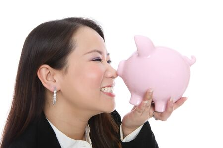 A pretty young asian woman smiling with piggy bank photo