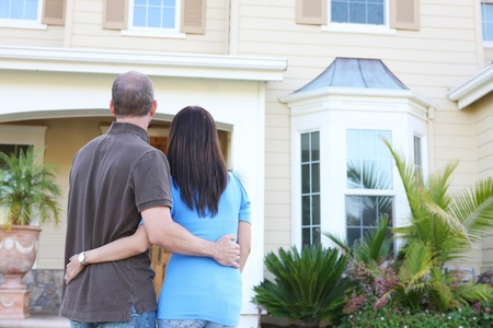 An attractive happy newlywed couple in front of their home in love photo