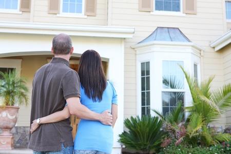 pareja en casa: Una pareja atractiva newlywed feliz en frente de su casa en amor