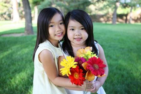 かわいい若いアジア女の子姉妹公園で花を持って