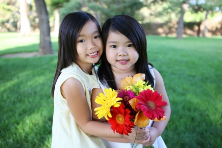 Cute young Asian girl sisters holding flowers in park Archivio Fotografico