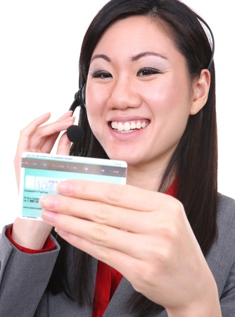 A asian business woman holding a credit card while ordering on the phone photo
