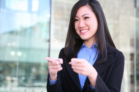 A pretty, young business woman pointing at office bu=ilding Stock Photo - 10184103