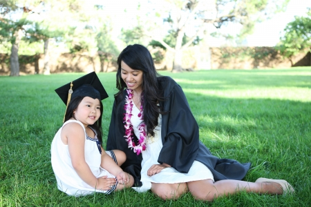 A pretty asian woman with daughter celebrating graduation in the park photo