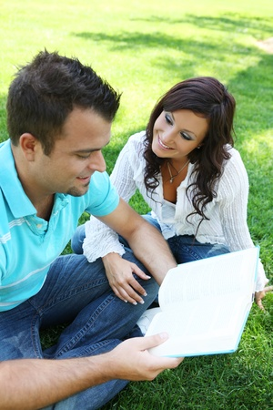 Attractive Couple studying on the grass in the park photo