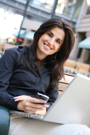 adult indian: A young pretty business woman ouside office building with laptop computer and smartphone Stock Photo