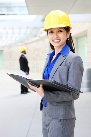 A young and pretty asian architect woman at building site  photo