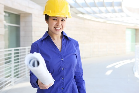 asian architect: A young and pretty asian builder woman at construction site