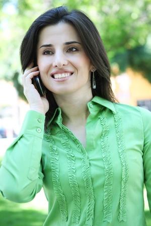 Een mooie, etnische vrouw op de telefoon buiten Stockfoto