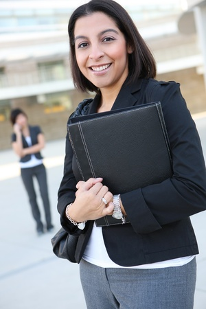 hispanic women: An attractive hispanic business worker with co-worker in background