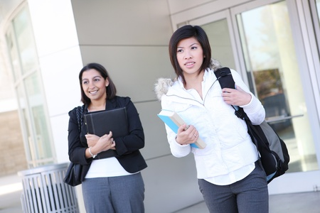 book jacket: Pretty young diverse women on university campus leaving class  Stock Photo