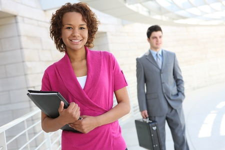 Une femme d'affaires belle africaine avec un co-travailleur en arrière-plan Banque d'images