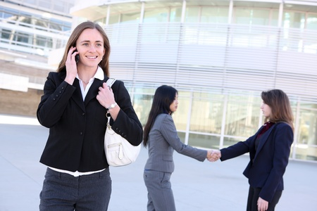 A  young business woman on the phone with coworkers shaking hands at office building photo