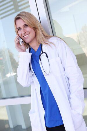 휴대 전화에 병원 밖에서 꽤 젊은 금발의 여자 간호사