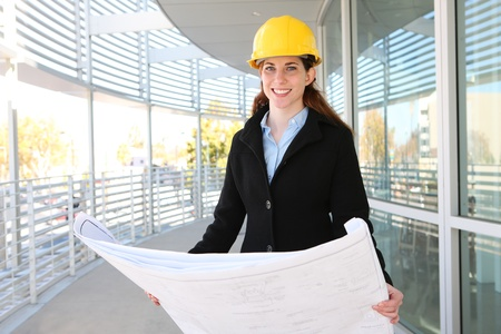 Woman Architect at work site with blueprints photo