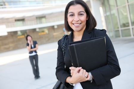 An attractive hispanic business worker with co-worker in background Stock Photo