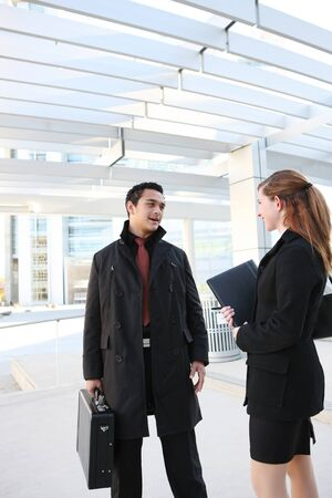 A Hispanic Man and Caucasian Business Woman at their company building  photo