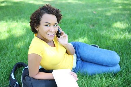 A pretty african american woman talking on the cell phone in park photo