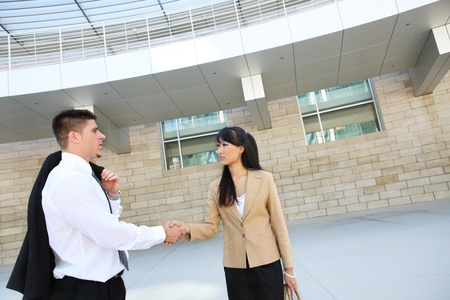 corporate buildings: A handsome caucasian business man shaking hands with woman