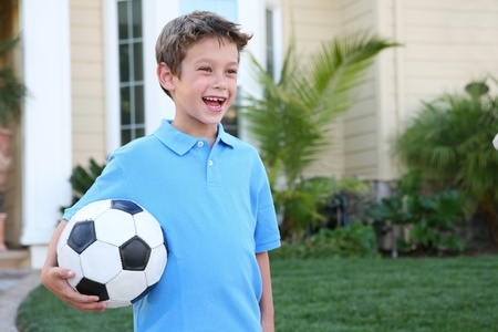A young boy outside home holding soccer (football) ball Standard-Bild