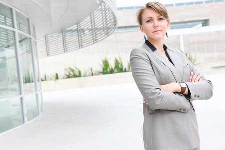A pretty business woman outside office building Standard-Bild