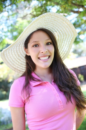 A cute teenage girl smiling in the park with straw hat Stock Photo - 10754717
