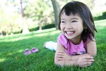 かわいい若いアジア女の子はリラックスできる公園