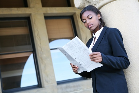 african american woman business: A young and pretty african american woman at college reading newspaper