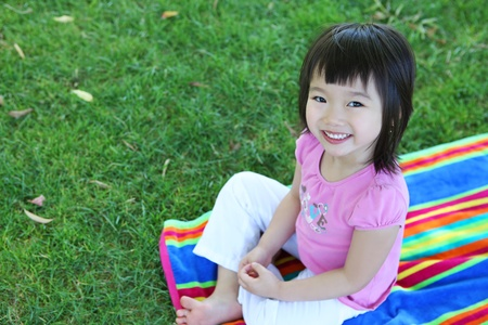 A cute young asian girl sitting on a rainbow colored towel on the grass Stock Photo - 10754718