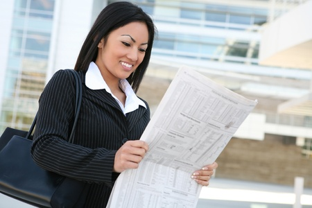 A pretty asian business woman reading the newspaper outside company  photo