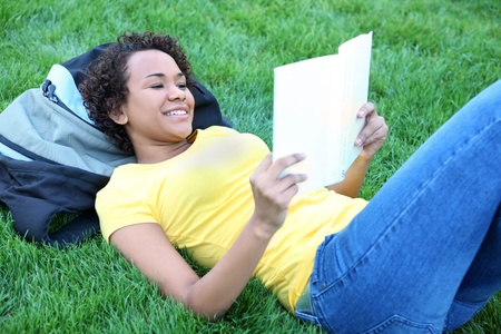 A pretty african american woman reading book in park  photo