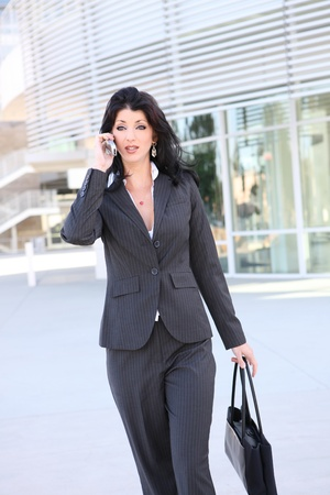 A pretty business woman on the phone at office building Stock Photo - 10830174
