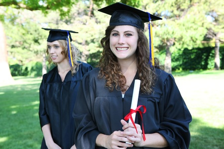 Pretty young woman at graduation holding diploma Stock Photo - 10907647