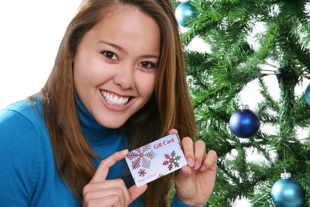 A pretty girl at Christmas holding a gift card  Stock Photo - 10907648