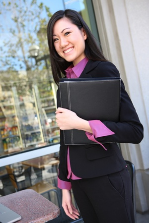 asian office lady: A pretty asian business woman with notebook at office building