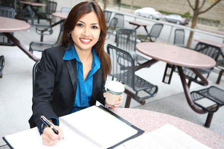 A pretty asian business woman at table with notebook photo