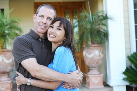 An attractive happy couple in front of their home in love photo