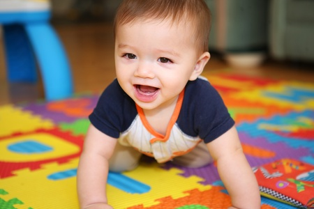 A cute young boy baby playing inside home with colorful toys Stock Photo - 12288269