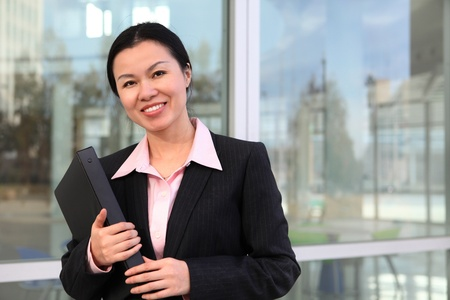 A pretty Chinese business woman smiling outside office building Stock Photo - 12288277