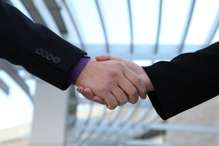 conclude: A man and woman handshake to conclude a successful business deal Stock Photo