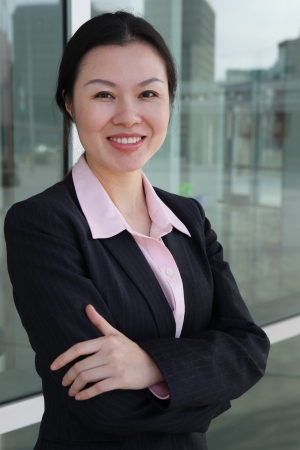 A pretty Chinese business woman smiling outside office building photo