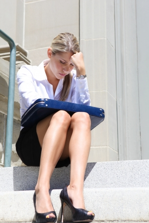 A upset, depressed business woman sitting outside company Stock Photo