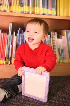A young baby boy happily playing in the library photo