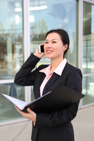 phone business: A pretty Chinese business woman smiling outside office building on phone