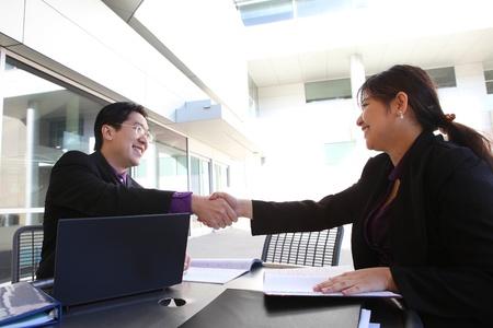 Een etnische man en vrouw business team handdruk op het kantoor gebouw Stockfoto