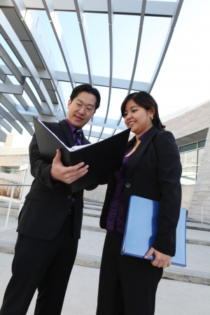 An ethnic man and woman business team looking at notebook photo