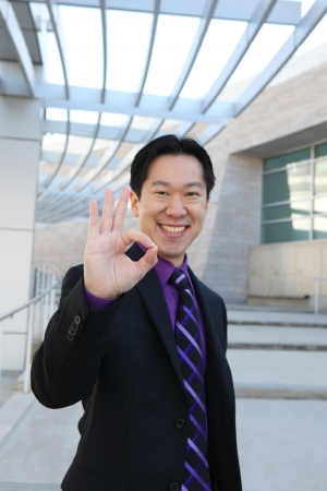 working class: A handsome Chinese business man at office building indicating success  Focus on Hand