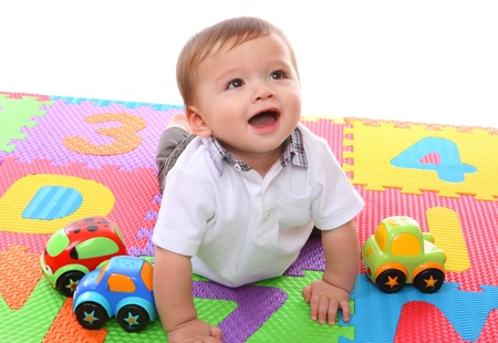 A cute young baby boy playing with his colorful toys photo