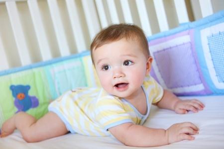 pie bebe: Un muchacho lindo beb� joven sonriente en una cuna
