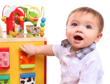 objects: A cute young boy playing with his colorful toys isolated over white